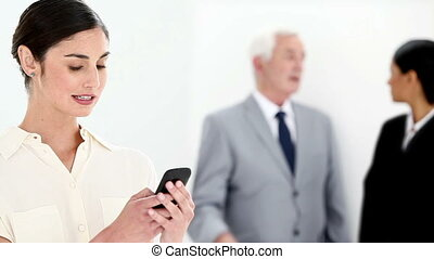 Businesswoman typing a text message with her colleagues in...