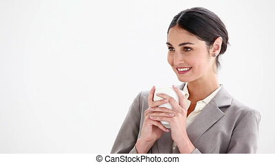 Businesswoman drinking from a cup against a white background