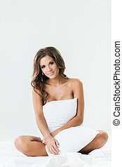 Nude smiling brunette sitting on a bed with pillow