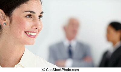 Beautiful woman posing with people talking in her back...
