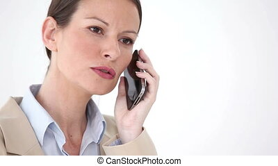 Serious woman in a suit on the phone against a white...