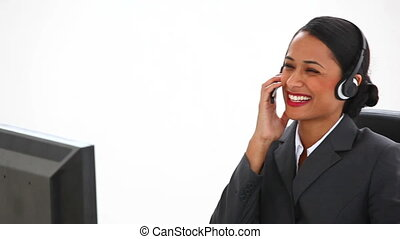 Businesswoman at her desk using a headset against white...