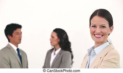Smiling businesswoman posing while colleagues are talking...