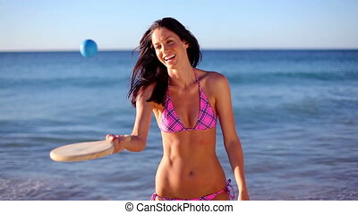 Smiling brunette playing with a paddle