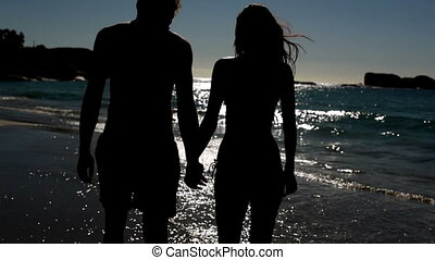 Relaxed couple standing under the moonlight on the beach