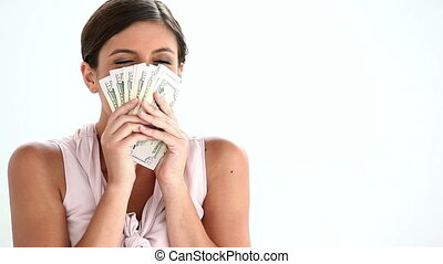 Woman smelling US banknotes against white background