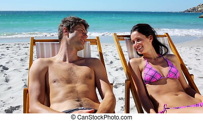 Happy couple lying on deck chairs on the beach