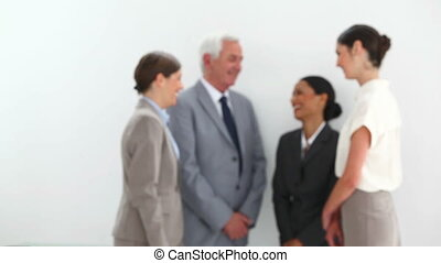 Happy businesswoman posing while her colleagues are talking