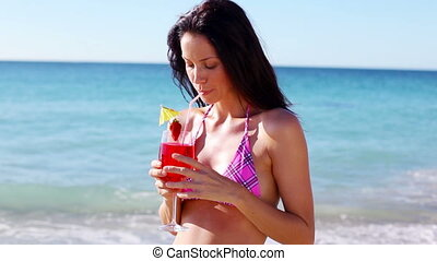 Smiling brunette drinking a cocktail on the beach