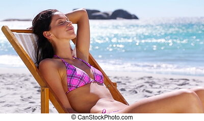 Brunette woman resting - Brunette woman resting on the beach...