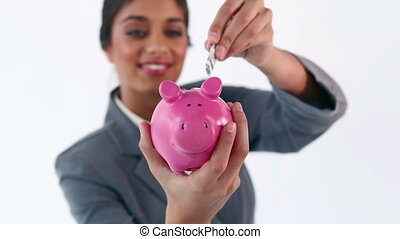 Smiling brunette putting notes in a piggy bank against a...