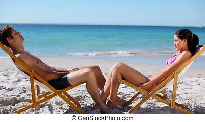 Couple talking while sitting on deck chairs on the beach