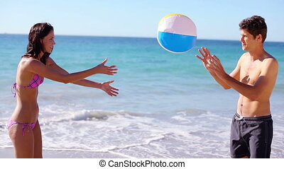 Smiling couple playing with a beach ball in front of the...