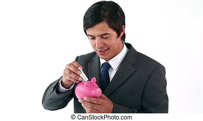 Smiling businessman holding a piggy bank against a white...