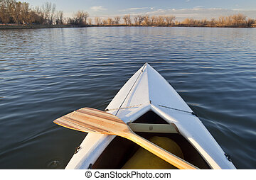 canoe bow and paddle - bow of white canoe with wooden paddle...