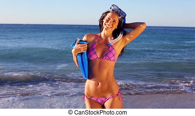 Smiling woman holding her swimming fins on the beach