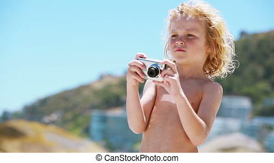 Child using a digital camera on the beach