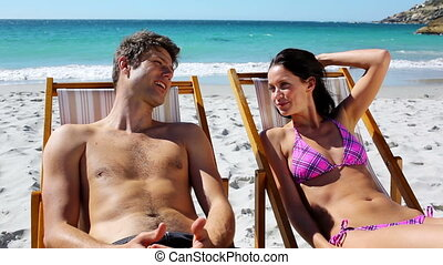 Lovely couple sitting on deck chairs on the beach