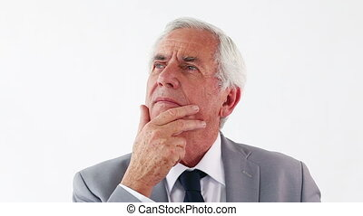 Thoughtful man placing his hand on his chin against a white...