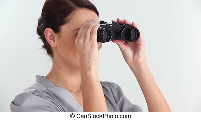 Beautiful woman looking through binoculars against white...