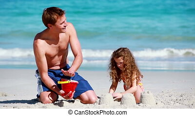 Man building a sand castle on the beach