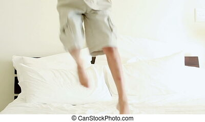 Smiling child jumping on a mattress in a bedroom