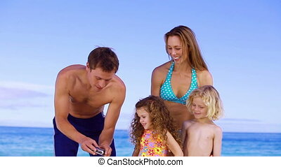 Happy family being photographed on the beach