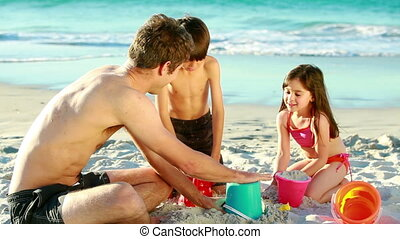 Happy family building sand castles on the beach