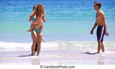 Smiling mother catching her daughter on the beach