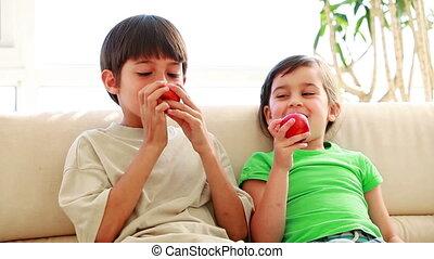 Peaceful siblings eating red apples in the living room