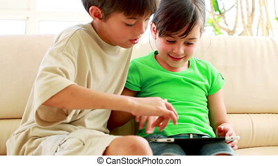 Children playing together with a tablet computer in the...