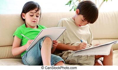 Happy siblings doing their homework