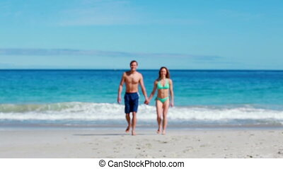 Lovely couple walking together on the beach