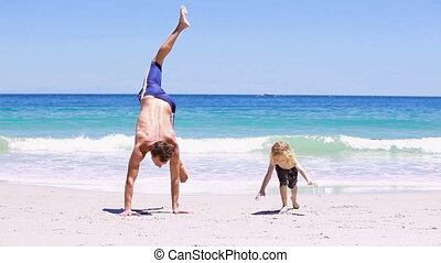 Smiling father doing handstands with his son
