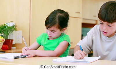 Serious siblings doing their homework in the kitchen