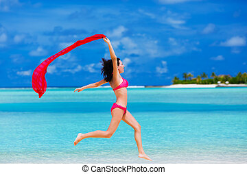 Young woman jumping on the beach with a red scarf -...