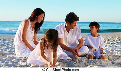 Cheerful family sitting on the sand
