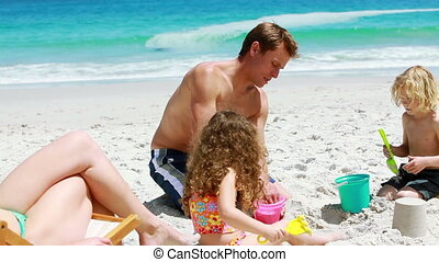 Father and his children building a sand castle on the beach