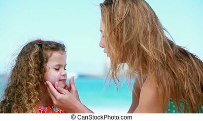 Mother applying sunscreen on a little girl on the beach