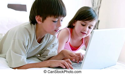 Siblings typing on a laptop in the bedroom