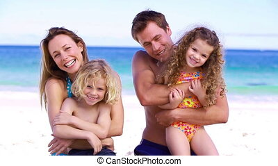 Parents hugging their children on the beach