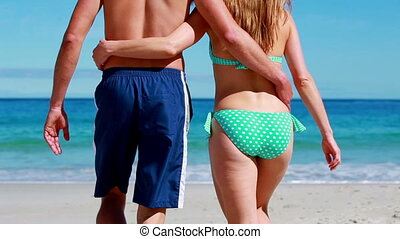 Happy couple walking while embracing on the beach