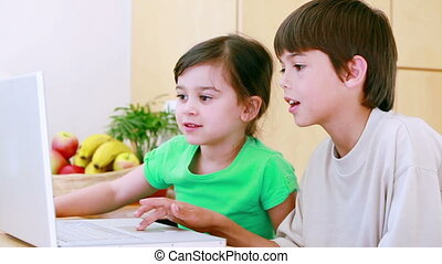 Happy children grimacing in front of a laptop in the kitchen