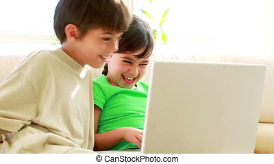 Siblings using a laptop together in the living room