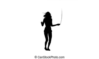 Silhouette of a woman using a skipping rope - A silhouette...
