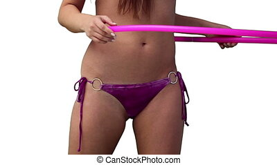 Close up of a woman spinning a hula hoop around her waist