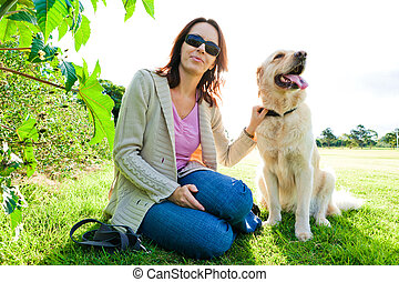 Young woman and golden retriever sitting in grass|