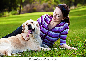 Young woman and golden retriever in the grass