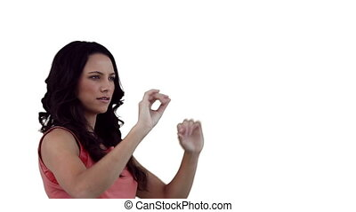 Brunette woman using a virtual touchscreen against a white...