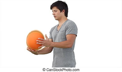 Man practising spinning a basketball against a white...